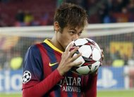 Barcelona's Neymar kisses the ball after scoring a hat-trick against Celtic as he leaves the pitch at the end of their Champions League soccer match at Camp Nou stadium in Barcelona December 11, 2013. REUTERS/Gustau Nacarino