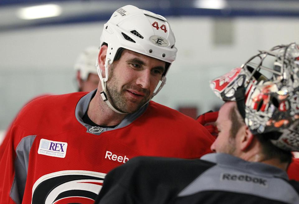Carolina Hurricanes' Jay Harrison, left, talks with Cam Ward during an informal workout for the NHL hockey team at Raleigh Center Ice on Friday, Sept. 14, 2012.  (AP Photo/The News & Observer, Ethan Hyman) MANDATORY CREDIT