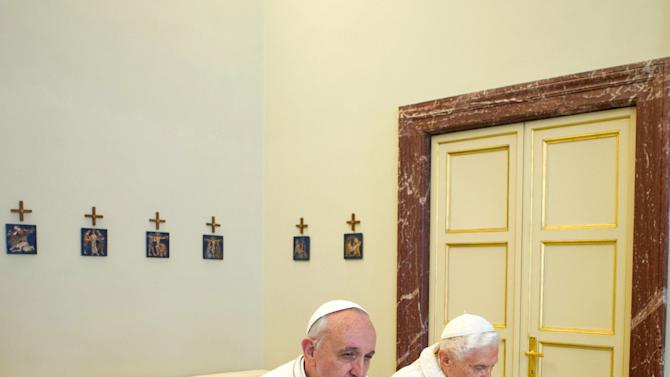 "In this photo provided by the Vatican paper L'Osservatore Romano, Pope Francis, left, and Pope emeritus Benedict XVI pray together in Castel Gandolfo Saturday, March 23, 2013. Pope Francis has traveled to Castel Gandolfo to have lunch with his predecessor Benedict XVI in a historic and potentially problematic melding of the papacies that has never before confronted the Catholic Church. The Vatican said the two popes embraced on the helipad. In the chapel where they prayed together, Benedict offered Francis the traditional kneeler used by the pope. Francis refused to take it alone, saying ""We're brothers,"" and the two prayed together on the same one. (AP Photo/Osservatore Romano, HO)"