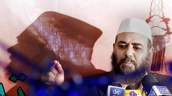 """Tarek el-Zomor leader and founder of the Building and Development Party, who was convicted with others of planning the assassination of late president Anwar in 1981, talks during a presser to celebrate the early results of an Islamist-backed constitution in Cairo, Egypt, Monday, Dec. 24, 2012. The Muslim Brotherhood, the main group backing the charter, claimed it passed with a 64 percent """"yes"""" vote. The official results are expected on Monday, Dec. 24. (AP Photo/Amr Nabil)"""