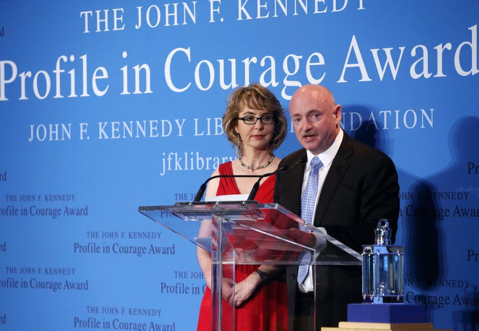 Former Arizona congresswoman Gabrielle Giffords, left, listens as her husband Capt. Mark Kelly speaks after Giffords received the John F. Kennedy Profile in Courage Award at the JFK Library in Boston, Sunday, May 5, 2013.  (AP Photo/Michael Dwyer)