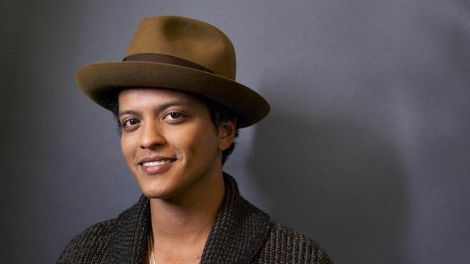 "FILE - This Nov. 5, 2012 file photo shows American performer Bruno Mars posing for a portrait in New York. WEtv announced Wednesday, April 10, 2013, that Grammy winner's four sisters will appear in a reality series documenting the recording process of their debut album. ""The Lylas"" will include Tiara, Tahiti and Presley, who are moving from Hawaii to Los Angeles to join older sister Jamie. (Photo by Dan Hallman/Invision/AP, file)"