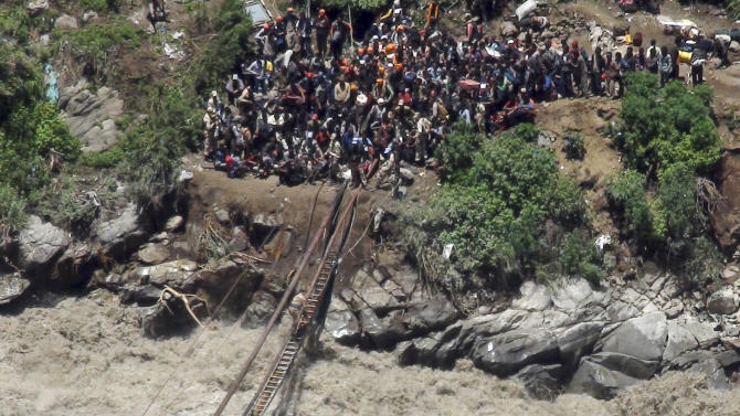 Indo-Tibetan Border Police (ITBP) personnel, in uniform, help stranded pilgrims on a makeshift bridge cross a stream of gushing floodwater at Govind Ghati, in Chamoli district, in northern Indian state of Uttarakhand, India, Friday, June 21, 2013. A top official in a northern Indian state hit by heavy monsoon rains said more than 500 people died in the flooding and landslides. The heavy rains caused by the annual monsoon have also stranded tens of thousands, mostly pilgrims, in the mountainous region. (AP Photo)