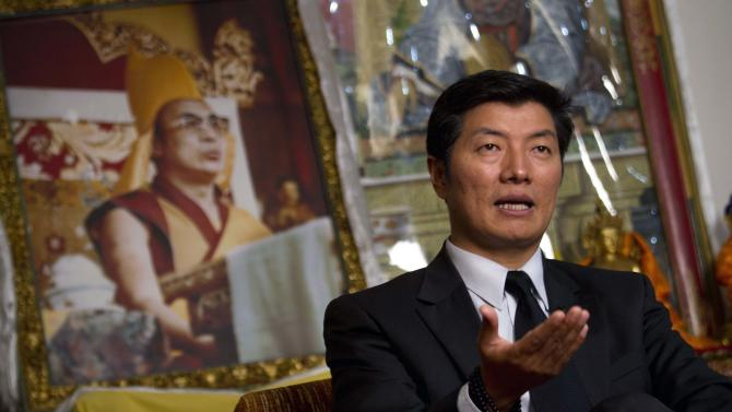 FILE - In this Feb. 14, 2012 file photo, Lobsang Sangay, the prime minister of the Tibetan government in exile, sits in front of a portrait of the Tibetan spiritual leader the Dalai Lama during an interview in Dharmsala, India. Sangay came to power in what might be the most critical moment for Tibet in a generation: A wave of Tibetans have burned themselves alive to protest Chinese rule, Beijing is undergoing a transfer of power and the 76-year-old Dalai Lama is speaking openly of his eventual death. (AP Photo/Ashwini Bhatia, File)
