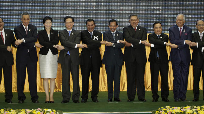 From left to right, Philippines' President Benigno Aquino III, Singapore's Prime Minister Lee Hsien Loong, Thailand's Prime Minister Yingluck Shinawatra, Vietnam's Prime Minister Nguyen Tan Dung, Cambodia's Prime Minister Hun Sen, Brunei's Sultan Hassanal Bolkiah, Indonesia's President Susilo Bambang Yudhoyono, Laos Prime Minister Thongsing Thammavong, Malaysia's Prime Minister Najib Razak and Myanmar's President Thein Sein holds hands during a group photo session for the 21st ASEAN Summit in Phnom Penh, Cambodia, Sunday, Nov. 18, 2012. (AP Photo/Vincent Thian)