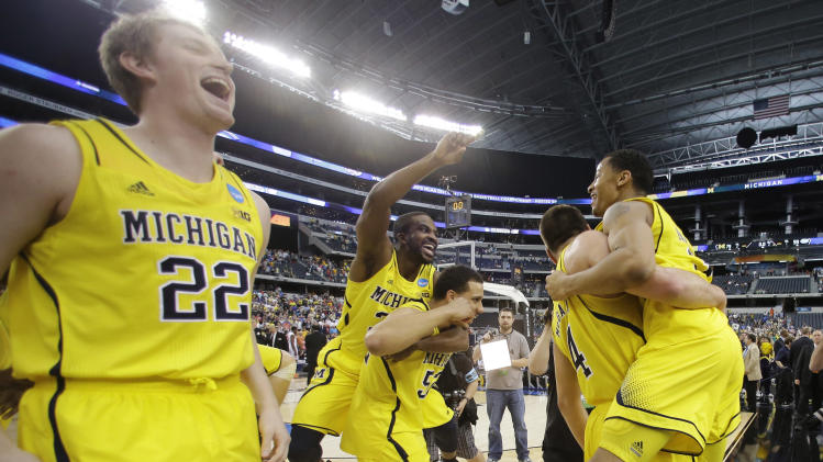 Michigan celebrates after a regional final game against Florida in the NCAA college basketball tournament, Sunday, March 31, 2013, in Arlington, Texas. Michigan won 79-59 to advance to the Final Four. (AP Photo/Tony Gutierrez)
