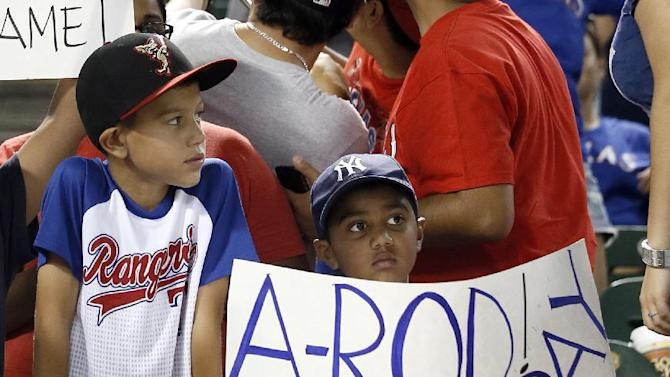 A pair of young fans hold a sign referencing New York Yankees' Alex Rodriguez after a baseball game against the Texas Rangers Monday July 27, 2015, in Arlington, Texas. (AP Photo/Tony Gutierrez)