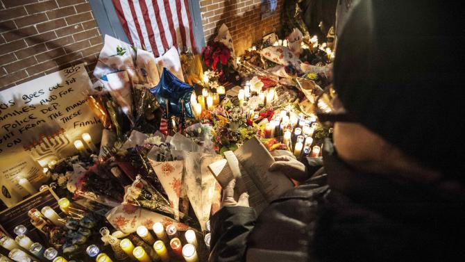 A woman recites from Bible while standing over makeshift memorial during prayer vigil at the site where two NYPD officers were fatally shot in Brooklyn borough of New York
