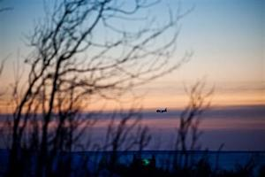 A passenger plane approaches Ted Stevens Anchorage International Airport on a cold and clear day in Achorage Alaska