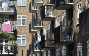 A man stands on a balcony in a residential high rise block of flats in Notting Hill in central London