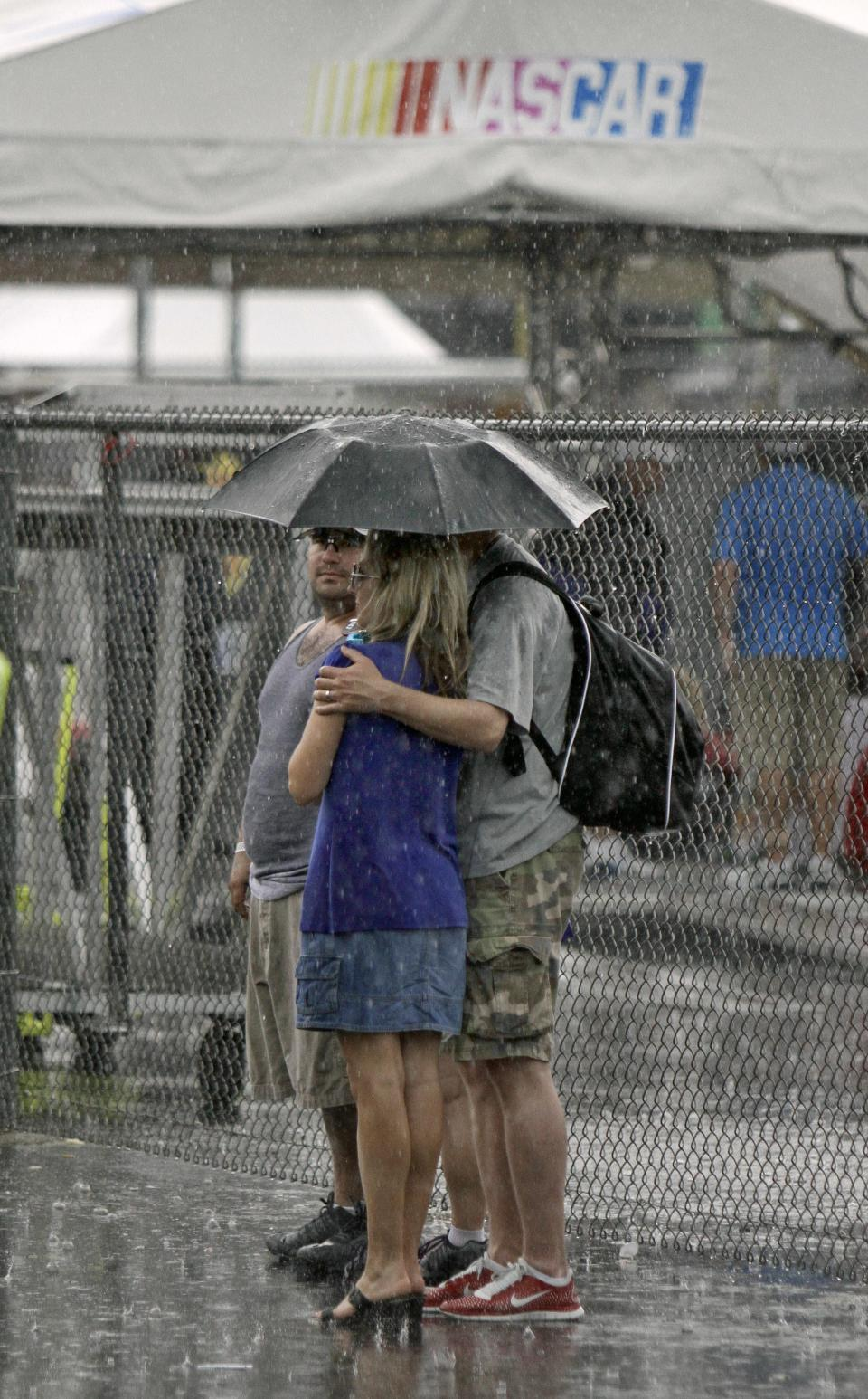 Fans huddle under an umbrella in the rain before scheduled start of the NASCAR Sprint Cup auto race at Kentucky Speedway in Sparta, Ky., Saturday, June 29, 2013. (AP Photo/Garry Jones)