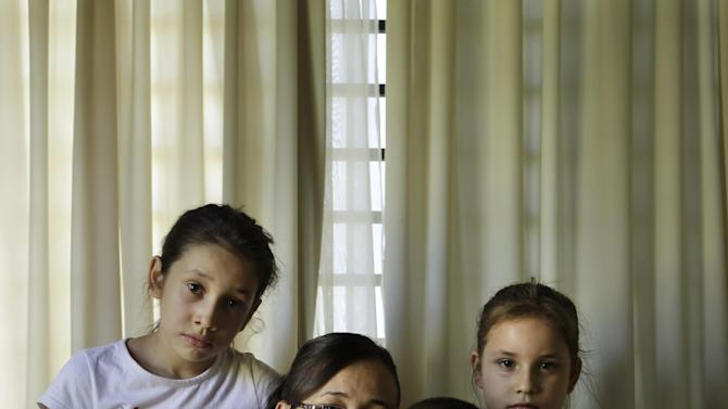 """In this Nov. 17, 2012 photo, Estela Meza poses with her children Stella Maris, 11, left, Lucia Belen, 7, right, and Erven Lucas, 4, as she holds a portrait of her late husband, Police Chief Erven Lovera, at their home in Asuncion, Paraguay.  Lovera was killed along with five other officers and 11 landless farmers during the """"Massacre of Curuguaty"""" on June 15 when negotiations between farmers occupying a rich politician's land ended with a barrage of bullets. (AP Photo/Jorge Saenz)"""