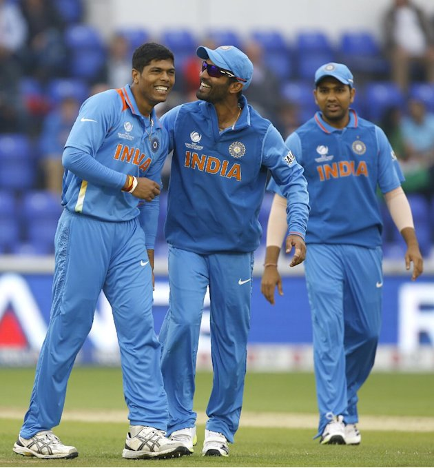 India's Umesh Yadav, left, and Dinesh Karthik, center, laugh after Yadav is accidentally knocked by the ball during an ICC Champions Trophy semifinal between India and Sri Lanka at the Cardiff Wales S