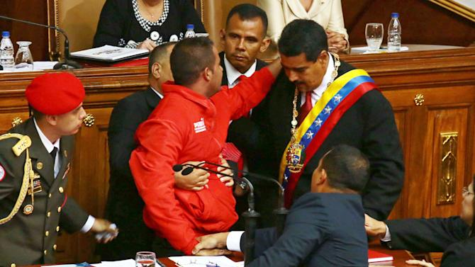"A spectator, center in red jacket, is surrounded by bodyguards after rushing to the podium where President Nicolas Maduro, right, was speaking at the start of his inauguration speech inside the National Assembly in Caracas, Venezuela, Friday, April 19, 2013.  Startling millions watching on national television, the man shouted into the microphone what sounded like ""Nicolas, my name is Jenry!"" before he was tackled and dragged away by security. (AP Photo/Francisco Boza)"