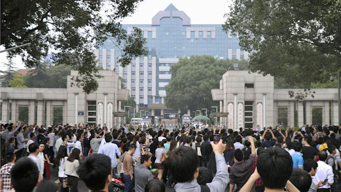 People gather in front of the city government office building in Zhejiang province's Ningbo city, protesting the proposed expansion of a petrochemical factory Saturday, Oct. 27, 2012. Thousands of people in the eastern Chinese city clashed with police while protesting the proposed expansion of the factory that they say would spew pollution and damage public health, townspeople said. (AP Photo/Kyodo News) JAPAN OUT, MANDATORY CREDIT, NO LICENSING IN CHINA, FRANCE, HONG KONG, JAPAN AND SOUTH KOREA