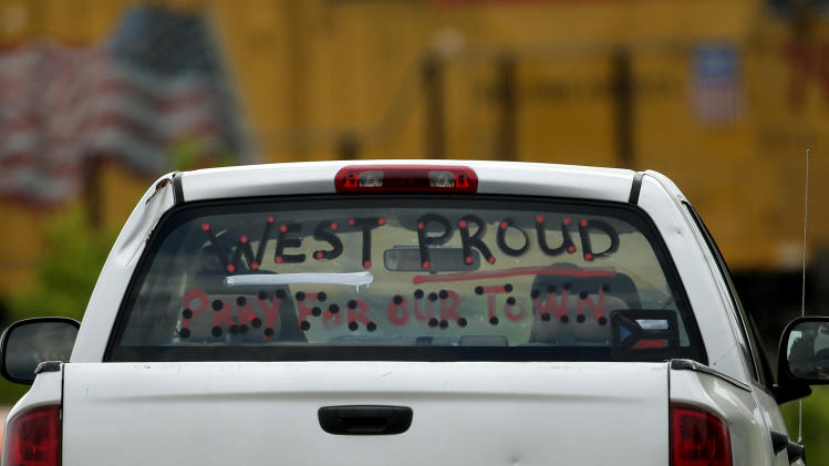 A sign is seen on a pickup window as it passes near the ruins of the West Fertilizer Co. Sunday, April 21, 2013, four days after an explosion at the plant in West, Texas. The massive explosion Wednesday night killed 14 people and injured more than 160. (AP Photo/Charlie Riedel)