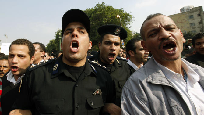 Egyptian policemen march in protest holding an Egyptian flag in Tahrir Square in Cairo, Egypt, Monday Feb. 14, 2011. Egypt's military rulers called for an end to strikes and protests Monday as thousands of state employees, including police, demonstrated to demand better pay in a growing wave of labor unrest unleashed by the democracy uprising that ousted Hosni Mubarak's regime(AP Photo/Hussein Malla)