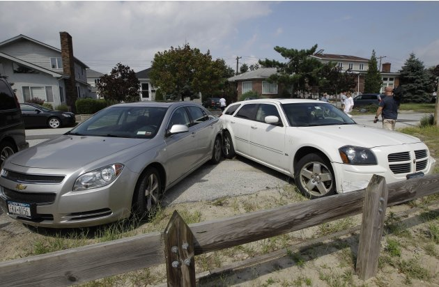 Two cars that collided into each other remain at a 45 degree angle after a possible tornado touched down in the Breezy Point neighborhood in New York, Saturday, Sept. 8, 2012.   A tornado swept out of