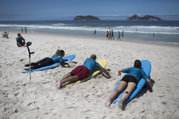 In this March 16, 2013 photo, surfing students exercise on their boards before hitting the waves at Barra da Tijuca beach in Rio de Janeiro, Brazil. Dozens of disabled people in Rio are conquering the