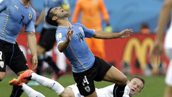 Uruguay's Nicolas Lodeiro is tripped up by England's Wayne Rooney during the group D World Cup soccer match between Uruguay and England at the Itaquerao Stadium in Sao Paulo, Brazil, Thursday, June 19, 2014. (AP Photo/Kirsty Wigglesworth)