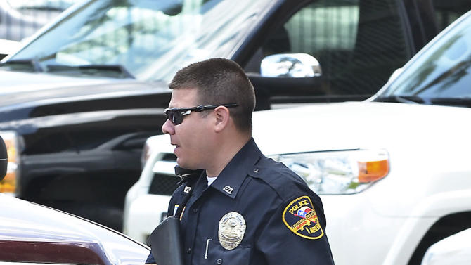 A member of the Laredo Police Department carries his weapon as he exits the Holiday Inn Civic Center in Laredo, Texas, Tuesday, June 19, 2012, where two young boys were shot. The infant died and the scene and the toddler is on life support at a local hospital. (AP Photo/The Laredo Morning Times, Ricardo Santos)
