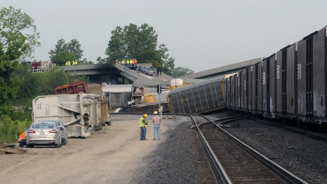 Officials survey the scene just east of the Route M overpass where several train cars derailed on the Burlington Northern Santa Fe train near Rockview, Mo. on Saturday, May 25, 2013. The National Transportation Safety Board has launched an investigation into the cause of a cargo train collision that partially collapsed a highway overpass in southeast Missouri, injuring seven people. (AP Photo/Southeast Missourian, Fred Lynch)