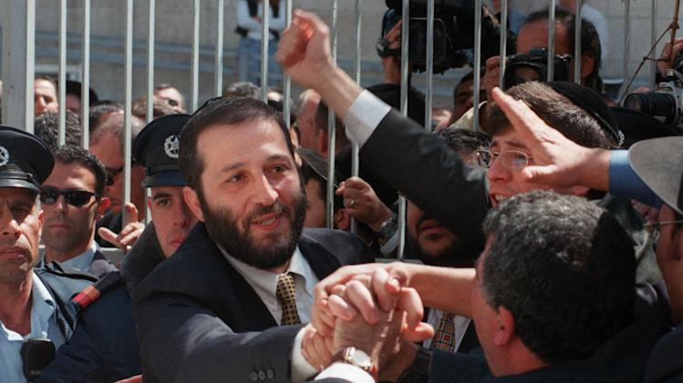 FILE - In this Wednesday, March 17, 1999 file photo, Arieh Deri, center, is greeted by supporters as he leaves the Jerusalem's district court after listening to his verdict. The popular ultra-Orthodox politician Deri is preparing a comeback after a 13-year hiatus that included a brief prison term for accepting bribes. (AP Photo/Eyal Warshavsky, File)