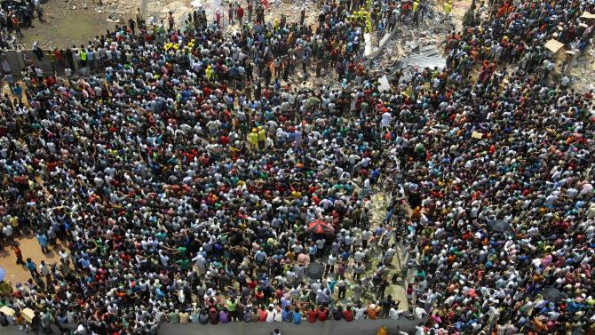 Bangladeshi people gather as rescuers look for survivors and victims at the site of a building that collapsed Wednesday in Savar, near Dhaka, Bangladesh,Thursday, April 25, 2013. At least 194 people died when a huge section of an eight-story building that housed several garment factories splintered into a pile of concrete. (AP Photo/A.M.Ahad)