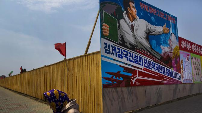 "FILE - In this Saturday, April 13, 2013 file photo, a North Korean woman walks past the outer wall of a construction site where a propaganda billboard depicting the launch of North Korean rockets in Pyongyang, North Korea. Worried that long-seething rifts could escalate over the South China Sea, Southeast Asian leaders are expected this week to press China to agree to start negotiations on a new pact aimed at thwarting a major clash in one of the world's busiest waterways. Concern over North Korea's latest threats is also expected to gain attention over economic issues in the annual summit of the Association of Southeast Asian Nations, or ASEAN, being held Wednesday, April 24 and Thursday, April 25 in Brunei's capital of Bandar Seri Begawan. The billboard reads: ""Lets open up an era to a strong economic country."" (AP Photo/David Guttenfelder, File)"