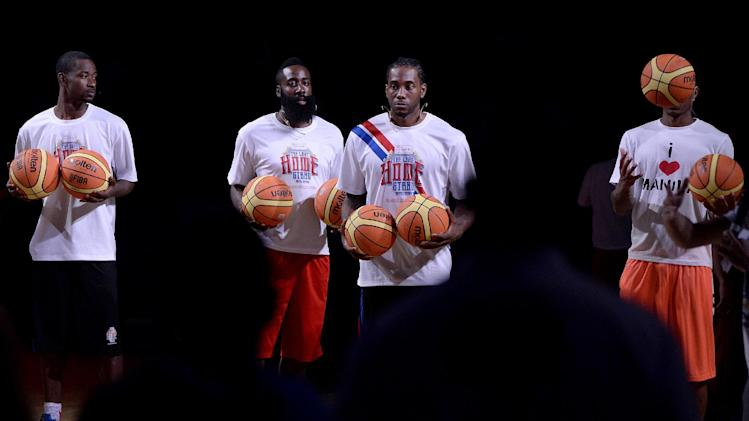 US NBA basketball players Terence Ross (L) of the Toronto Raptors, James Harden (C) of the Houston Rockets and Kawhi Leonard (R) of the San Antonio Spurs hold basketballs at the Araneta Coliseum in Manila on July 22, 2014