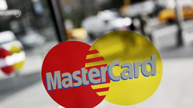 FILE- This Sept. 21, 2011, file photo. shows a MasterCard sign on a revolving door in New York. MasterCard reports quarterly financial results on Thursday, Oct. 30, 2014. (AP Photo/Mark Lennihan, File)