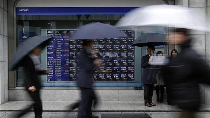 Pedestrians holding an umbrella walk past an electronic board displaying stock prices outside a brokerage in Tokyo December 19, 2013. REUTERS/Yuya Shino/Files