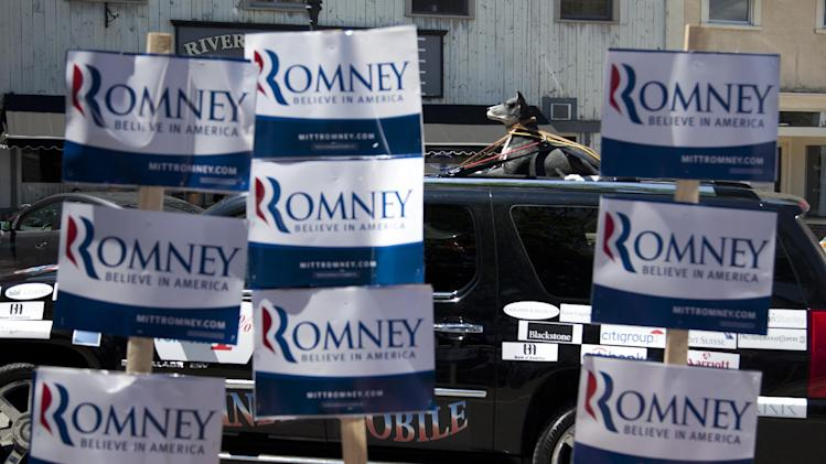 A protestor in a car circles a campaign event site for Republican presidential candidate, former Massachusetts Gov. Mitt Romney with a plastic dog strapped to the roof of their car, Friday, June 15, 2012, in Milford, N.H .  (AP Photo/Evan Vucci)