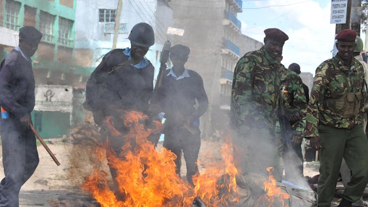 Kenyan police extinguish fire set on a road block, during riots  in Eastleigh, Nairobi, Kenya, Monday, Nov. 19, 2012. Police in Kenya have fired bullets into the air and tear gas into the streets to stop two groups from clashing one day after an improvised explosive device ripped through a bus and killed seven people.  Alfred Mutua, a witness to Monday's clashes in downtown Nairobi, said people are angry at ethnic Somalis, whom many Kenyans broadly blame for a series of grenade and explosive device attacks in Kenya over the last year. Mutua said others are trying to take advantage of the chaos by looting shops. (AP Photo)