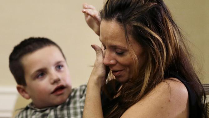 Plaintiff Michael McDonnell's son Sean, 6, wipes tears from Debra Bashwinger's face, Michael McDonnell's wife, during a news conference Tuesday, Sept. 18, 2012, in Philadelphia. Nine plaintiffs allege in civil lawsuits filed Tuesday that the Archdiocese of Philadelphia covered up child sex assault allegations made against seven Roman Catholic priests. (AP Photo/Matt Rourke)
