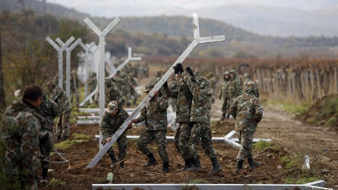 Macedonian soldiers erect a metal fence on the border with Greece, near Gevgelija