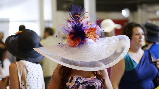 Lindsey Bowman, of Louisville, Ky., wears a big hat as she walks along the concourse at Pimlico Race Course, Saturday, May 18, 2013, in Baltimore. The 138th Preakness Stakes horse race takes place Saturday. (AP Photo/Nick Wass)