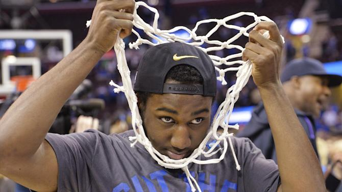 Kentucky's Dominique Hawkins pulls the net over his head during the celebration after Kentucky's 68-66 win over Notre Dame in a college basketball game in the NCAA men's tournament regional finals, Saturday, March 28, 2015, in Cleveland. Kentucky remains unbeaten and is headed for the Final Four ion Indianapolis. (AP Photo/David Richard)