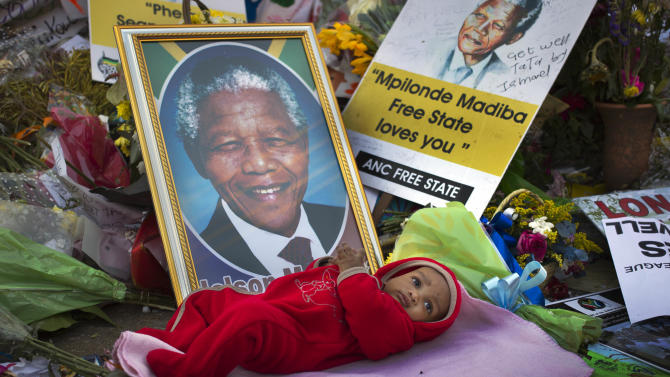 Oamohetswe Mabitsela, 4 months old, is placed by his mother next to a picture of Nelson Mandela for her to take a photograph of him with her camera phone, outside the Mediclinic Heart Hospital where former South African President Nelson Mandela is being treated in Pretoria, South Africa Thursday, July 4, 2013. The remains of Nelson Mandela's three deceased children were reburied at their original resting site on Thursday, a day after a court ordered their return two years after Mandela's grandson moved the bodies. (AP Photo/Ben Curtis)