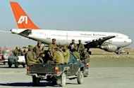 Afghan soldiers head towards the hijacked Indian Airlines plane at Kandahar airport in December 1999. Police in Indian Kashmir have arrested a militant suspected of involvement in the 1999 hijacking of an Indian passenger plane that was flown to Afghanistan, a government spokesman has told AFP