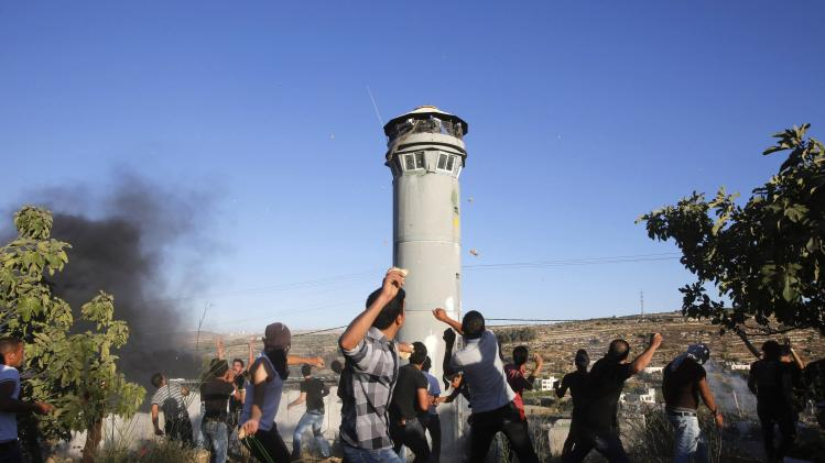 Palestinians throw stones at members of the Israeli army during the funeral of three Palestinians in Beit Ommar