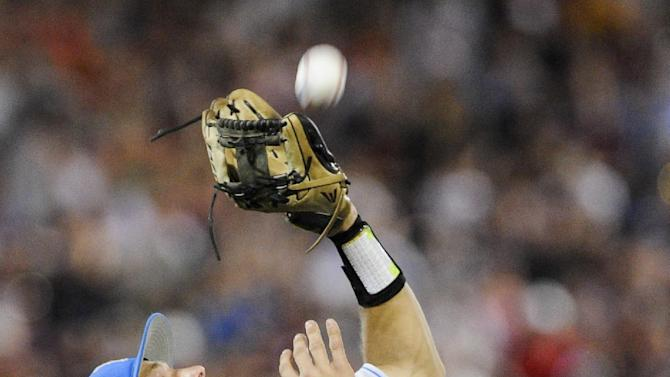 Mississippi State's Hunter Renfroe flies out to UCLA shortstop Pat Valaika in the sixth inning of Game 1 in their NCAA College World Series baseball finals, Monday, June 24, 2013, in Omaha, Neb. (AP Photo/Eric Francis)