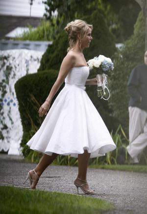 Actress Cheryl Hines walks across a lawn to the tent where her wedding to Robert F. Kennedy Jr., will take place in Hyannis Port, Mass. on Saturday, Aug. 2, 2014. (AP Photo/Stew Milne)