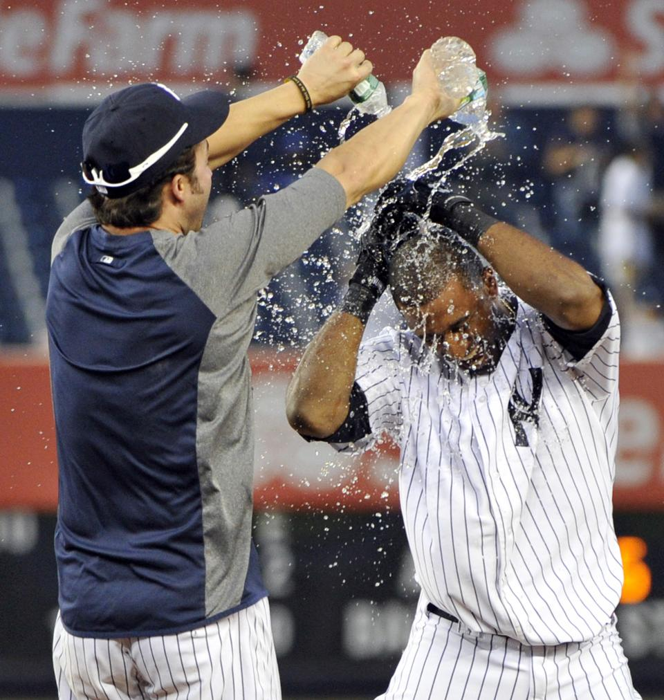 New York Yankees' Nick Swisher, left, douses teammate Eduardo Nunez with water after they defeated the Oakland Athletics 10-9 during the 14th inning of a baseball game on Saturday, Sept. 22, 2012, at Yankee Stadium in New York. (AP Photo/Bill Kostroun)