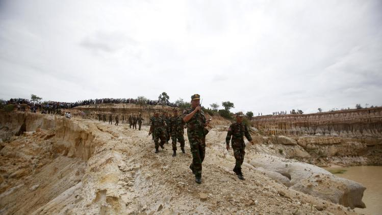 Cambodian soldiers arrive at the site where a Cambodian military helicopter crashed on the outskirts of Phnom Penh