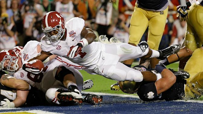 Alabama's T.J. Yeldon (4) dives into the end zone for a touchdown during the first half of the BCS National Championship college football game against Notre Dame Monday, Jan. 7, 2013, in Miami. (AP Photo/David J. Phillip)