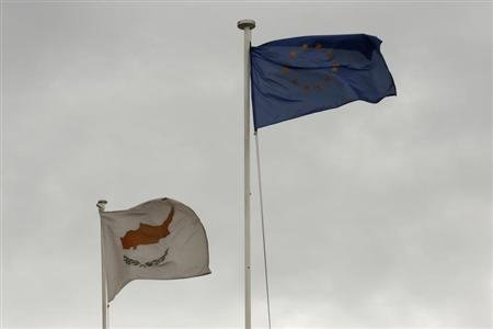 EU and Cypriot flags flutter atop the Presidential palace in Nicosia