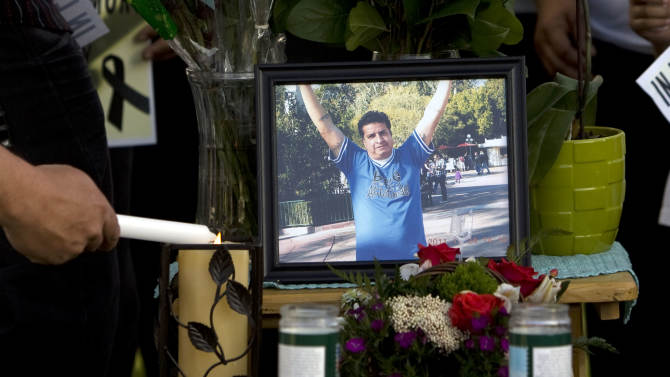 A mourner light candles at a makeshift memorial before a news conference by the family to discuss the death of Ricardo Portillo, who passed away after injuries he sustained after an assault by a soccer player at a soccer game he was refereeing on April 27, in Salt Lake City on Sunday, May 5, 2013. (AP Photo/The Salt Lake Tribune, Kim Raff)