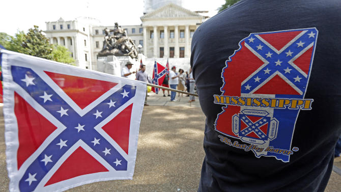 A member of the Sons of Confederate Veterans waves a small Confederate battle flag as he waits for a save the flag rally to begin on the steps of the Capitol in Jackson, Miss., Monday, July 6, 2015.  (AP Photo/Rogelio V. Solis)