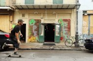 A man skateboards past a bar with boarded windows in the French Quarter in preparation for Hurricane Isaac in New Orleans, Louisiana